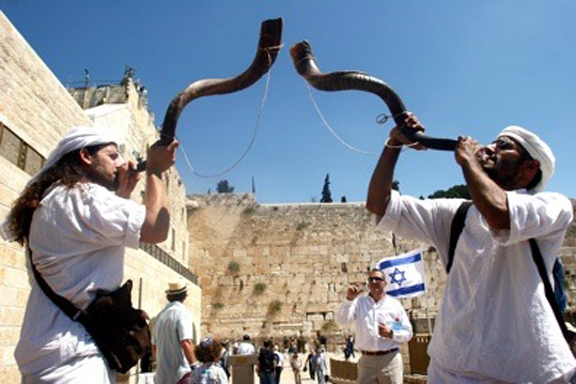 A Jewish man blows the Shofra at the Western Wall in the Old City of Jerusalem
